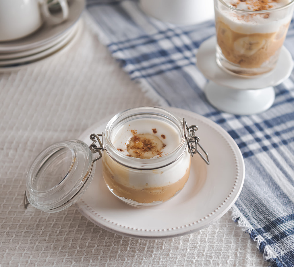Banoffee pie in a mason jar on a white ceramic plate with blue checkered tablecloth