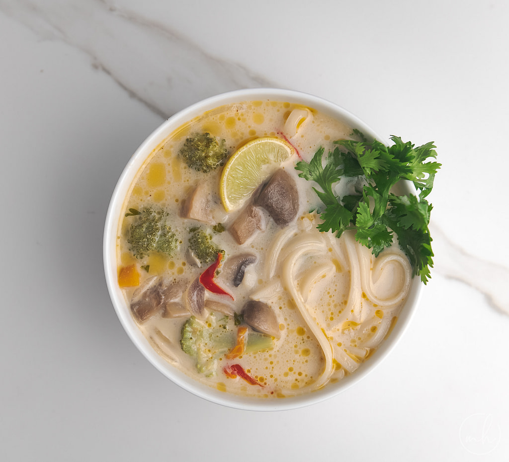 A bowl of thai mushroom coconut milk soup, garnished with coriander leaves. The bowl is placed on a piece of kitchen cloth.