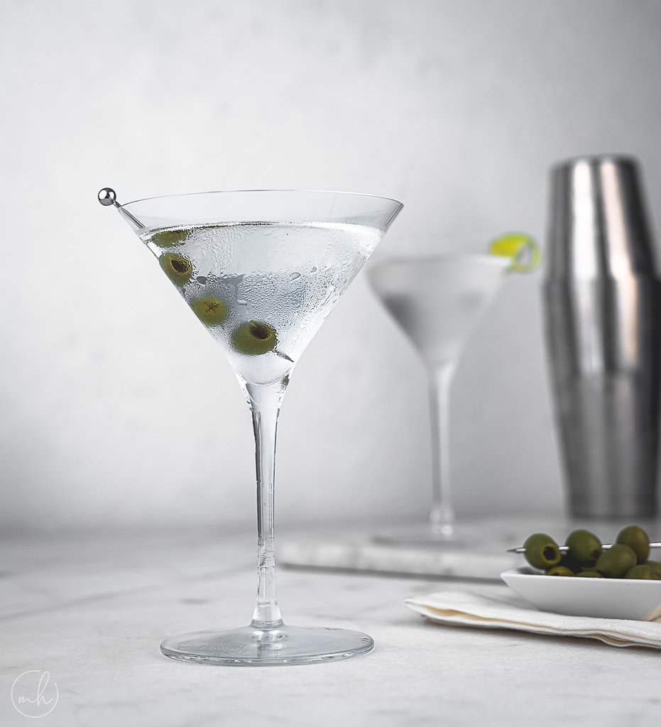 A martini cocktail glass with olives as garnish. In the backgroun, another martini glass, a bowl of olives and a shaker is placed.