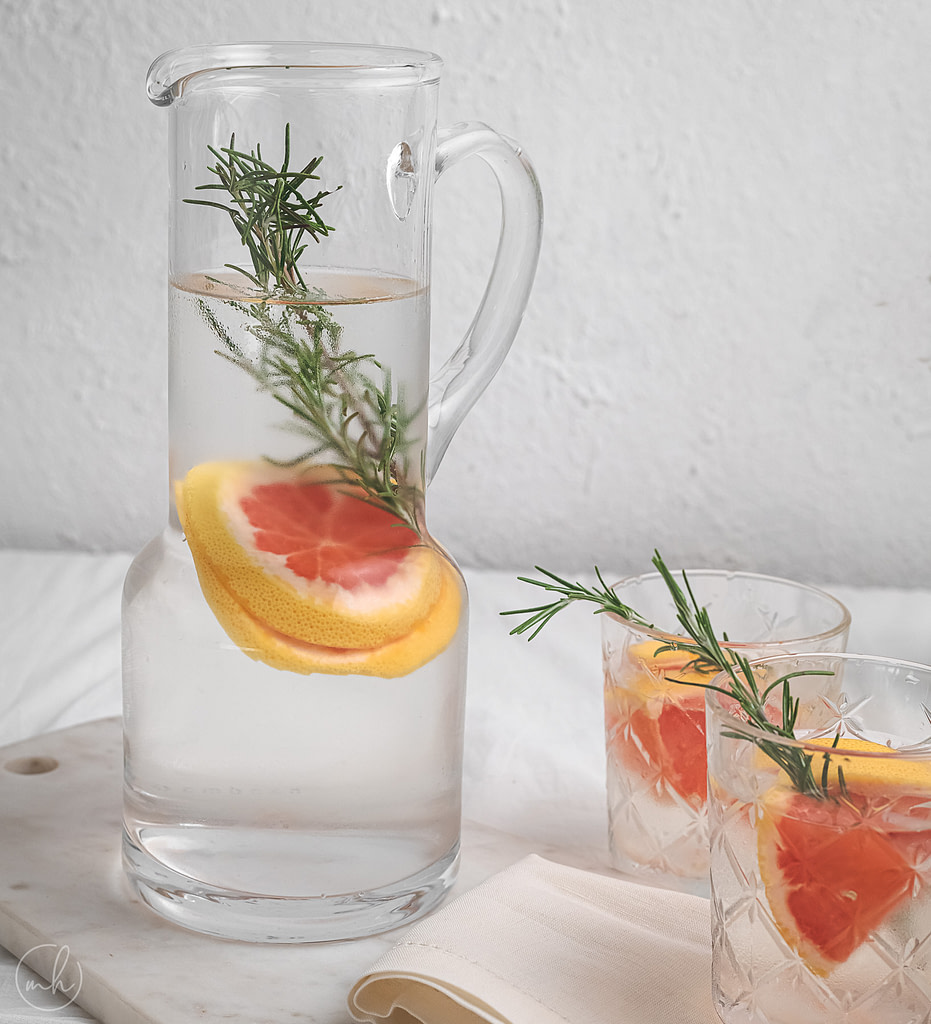 Rosemary grapefruit infused water served in a glass jar and two glasses. It is placed on a marble slate with a cotton cloth. A small pot with white flowers is placed in the background.
